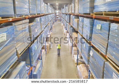 Warehouse manager holding laptop in aisle - stock photo