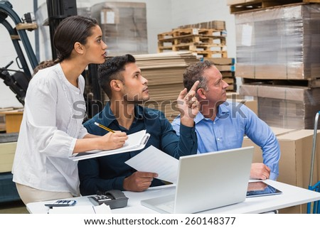 Warehouse manager pointing something to his colleagues in a large warehouse - stock photo