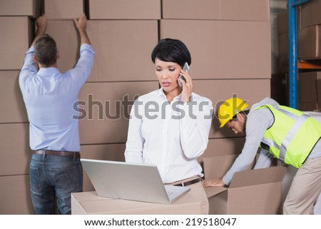 Warehouse manager using laptop and talking on phone in a large warehouse - stock photo