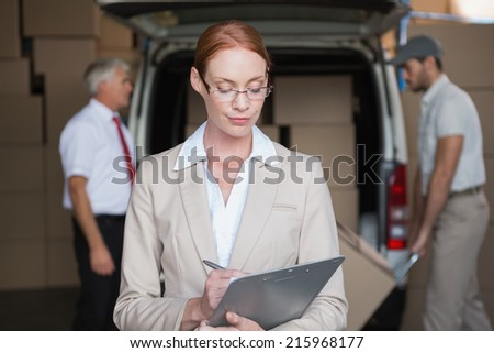 Warehouse manager writing in clipboard with delivery in background in a large warehouse - stock photo