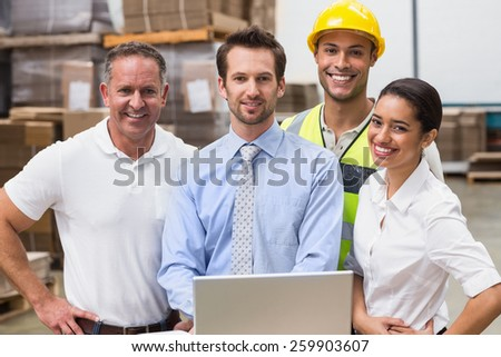 Warehouse managers and worker smiling at camera in a large warehouse - stock photo