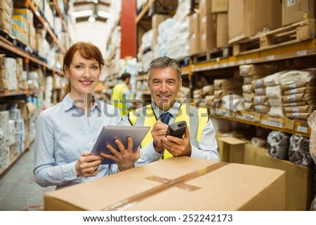 Warehouse managers smiling at camera in a large warehouse - stock photo