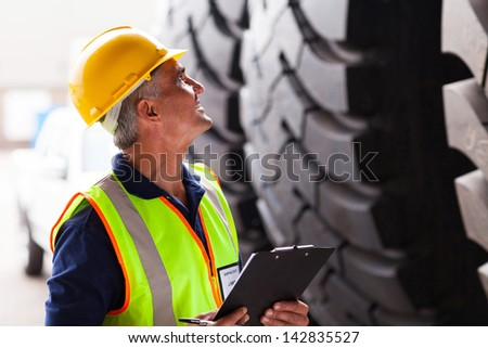warehouse middle aged worker inspecting industrial tires before exporting - stock photo