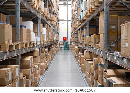 Warehouse rows with cardboard boxes and goods at shelves - stock photo