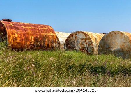 Warehouse storage of petroleum products in the old rusty barrels on the beach creates the danger of ecological disaster at the equator of the Black Sea, Ukraine, Snake Island  - stock photo