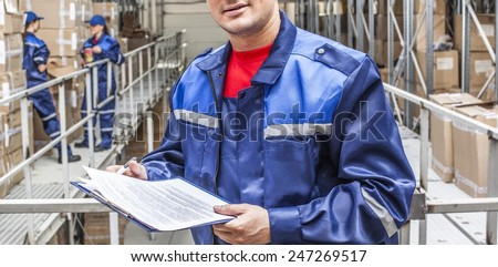 warehouse three workers- one man and two woman in a special blue uniform is recording and accounting of contents in cardboard boxes in stock No faces idea account statistics cargo arrival No face - stock photo