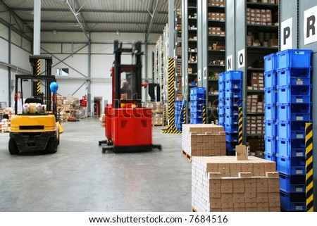Warehouse with pallet trucks working - stock photo