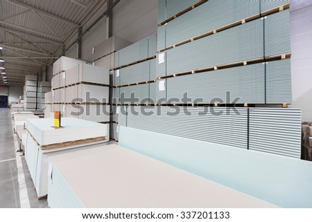 warehouse with piles of construction plasterboard - stock photo