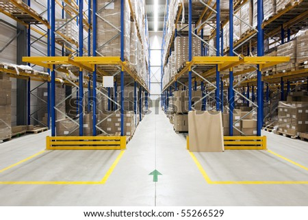 Warehouse with racks and shelves, filled with cardboard boxes, wrapped in foil on wooden pallets - stock photo