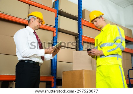 Warehouse Worker Checking The Inventory With Manager In A Large Warehouse - stock photo