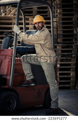 Warehouse worker climbing into fork lift - stock photo