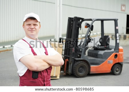 warehouse worker driver in uniform loading cardboard boxes by forklift stacker loader - stock photo