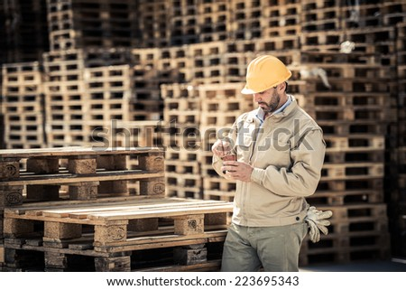 Warehouse worker having a break with coffee - stock photo