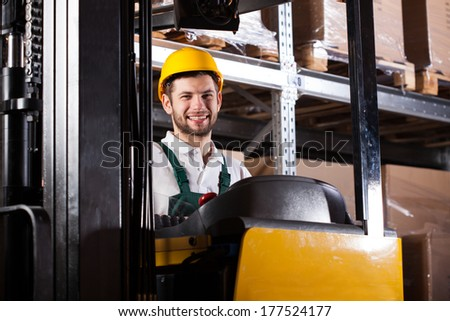 Warehouse worker in yellow hardhat working on forklift and smiling - stock photo