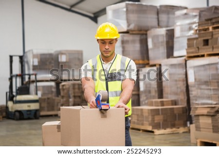 Warehouse worker preparing a shipment in a large warehouse - stock photo