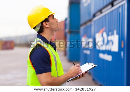 warehouse worker recording containers in shipping company - stock photo