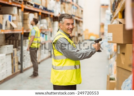 Warehouse worker scanning barcode on box in a large warehouse - stock photo