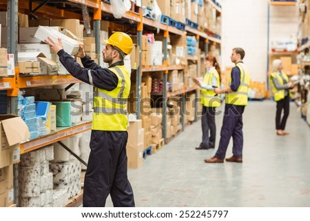 Warehouse worker taking package in the shelf in a large warehouse in a large warehouse - stock photo
