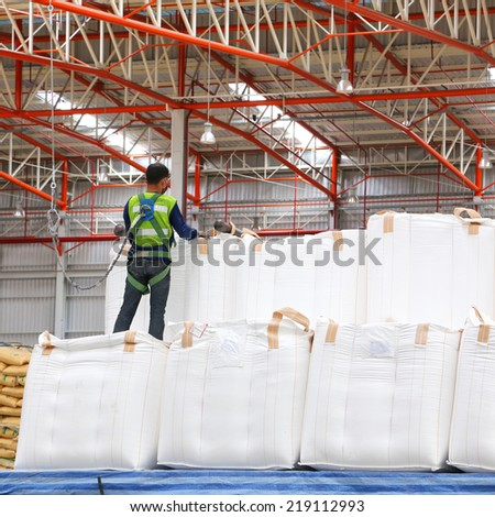 Warehouse worker wearing safety harness and safety line working on big bag stack  - stock photo