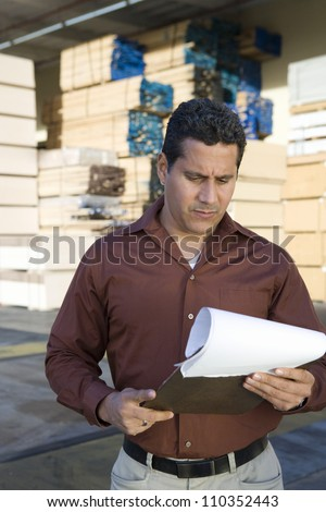 Warehouse worker with clipboard - stock photo