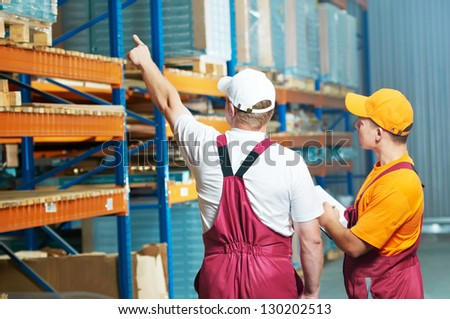 warehouse workers men inspecting and checking rack arrangement of furniture laminate flooring - stock photo