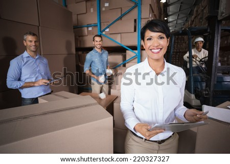 Warehouse workers preparing a shipment in a large warehouse - stock photo
