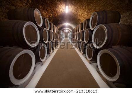 Warehoused barrels in the wine cellar - stock photo