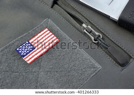 Warm Army or Soldier Coat Or Bag With American Flag Patch, Locked Zipper and Battle or Fight Knife, Military Or Army Concept, Closeup - stock photo