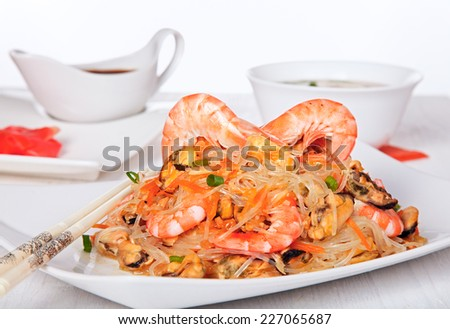 Warm asian salad with cellophane noodles, shrimp and mussels. - stock photo