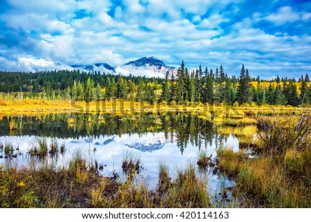 Warm autumn in the Rocky Mountains of Canada. Patricia Lake amongst the evergreen forests, yellow bushes and distant mountains - stock photo