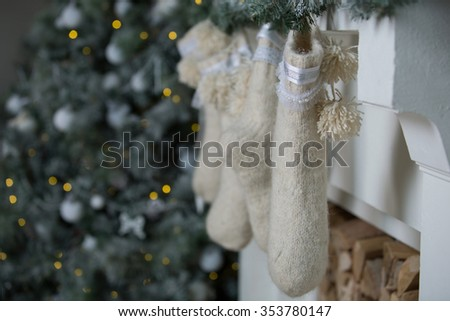 Warm Christmas socks over the fireplace with firewood. Christmas decorations - stock photo