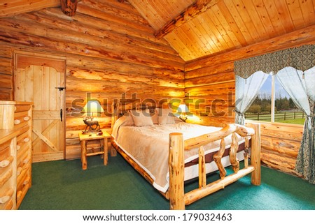 Warm cozy bedroom with rustic bed, nightstand and dresser. Green carpet floor and curtains. Log cabin house interior - stock photo