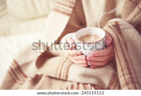 warm cup of hot coffee warming in the hands of a girl - stock photo