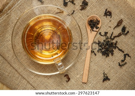 Warm cup of tea and leaves tea on burlap background - stock photo