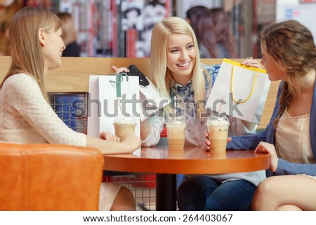 Warm friendly talk by the cocktail. Three charming young ladies having an exciting conversation sitting at the caf�© in shopping mall - stock photo
