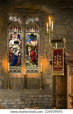 warm glowing church interior with stained glass window and lit glowing candles - stock photo