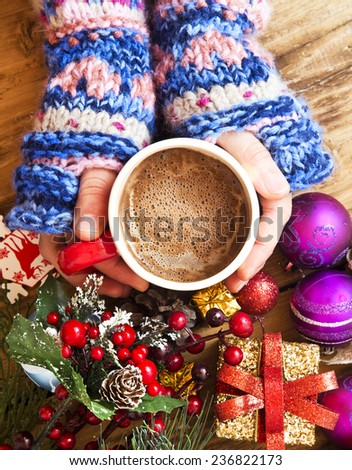 Warm Hands Holding Chocolate Cup with Christmas Decorations - stock photo