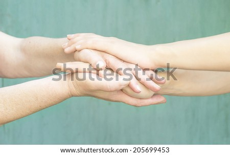 warm hands of a young girl and an old woman - stock photo