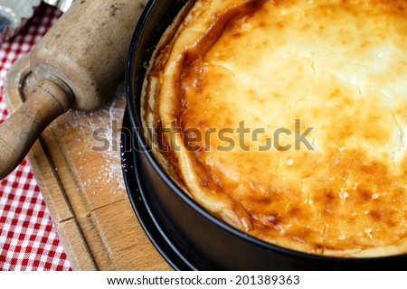 Warm home-made cheesecake in baking mould fresh out of the oven - stock photo
