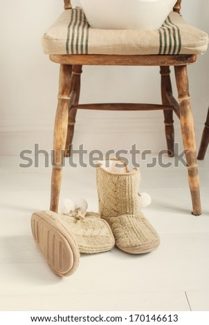 Warm House Slippers in front of wooden chair, toned - stock photo