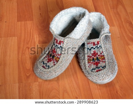 Warm knitted wool slippers with ornament on wooden floor close up. - stock photo