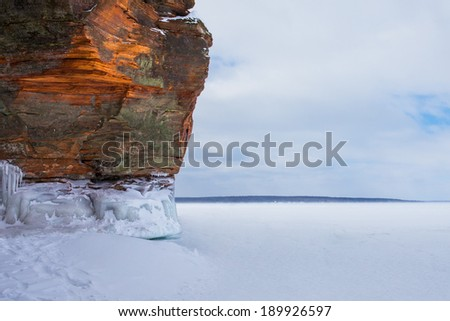Warm light on rocky cliff / shoreline of a frozen Lake Superior.  Highly textured rock.  Lots of copy space to the right.  Apostle Island National Lakeshore.  A popular travel destination in winter. - stock photo