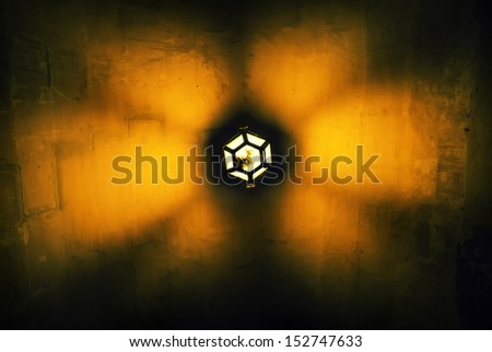 Warm light radiating out of an overhead street light - stock photo