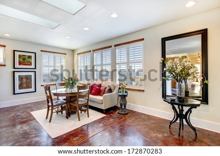 Warm light tones dining room with a rustic table set, water view and concrete modern floor. - stock photo