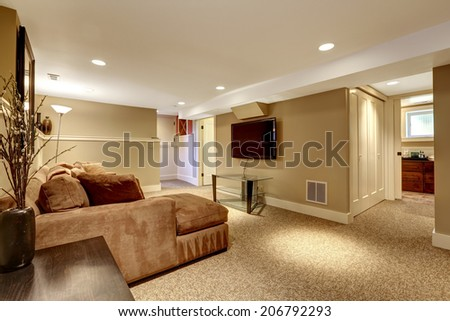 Warm living room interior in soft brown colors with comfortable sofa, glass top table and tv - stock photo