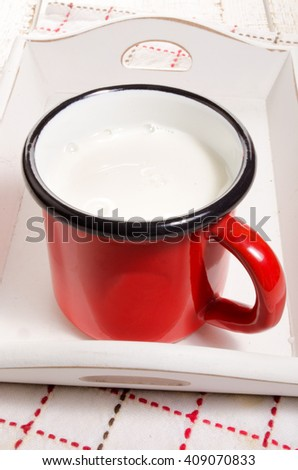 warm milk in a red enamel mug on a wooden serving tray - stock photo
