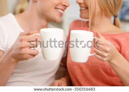 Warm moments. Young smiling couple looks at each other lovingly while holding tea mugs.  - stock photo