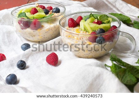 Warm oatmeal, chia seed, peanut butter, fresh corn in rice milk, garnished with kiwi, blueberries and raspberries and spring crushed mixed cashew, almonds and peanut. Selective focus at garnishes.  - stock photo
