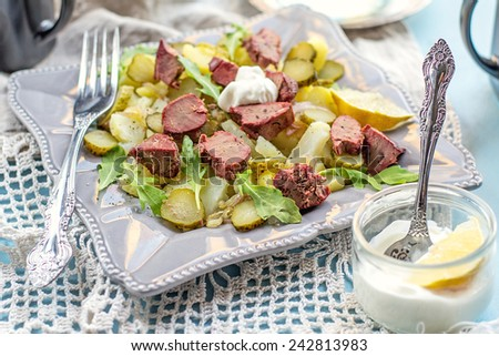 Warm salad with potatoes, pickles, chicken liver and mayonnaise. Shallow depth of field. Selective focus - stock photo