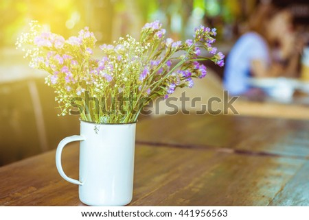 Warm scene with vintage flowers on wooden in cafe background, Bouquet flower - stock photo